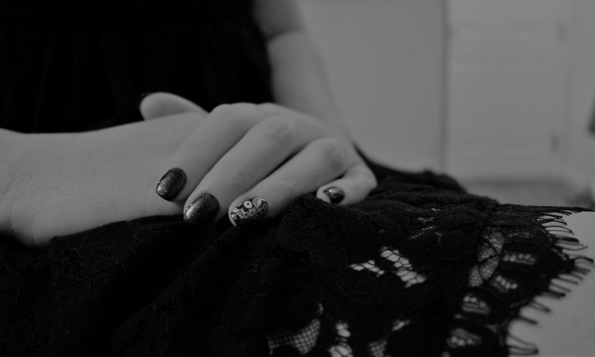 painted nails resting on black lace dress